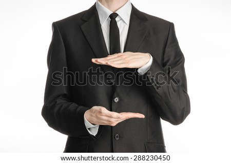 Businessman and gesture topic: a man in a black suit and tie holding two hands in front of him and shows the size on white isolated background in studio