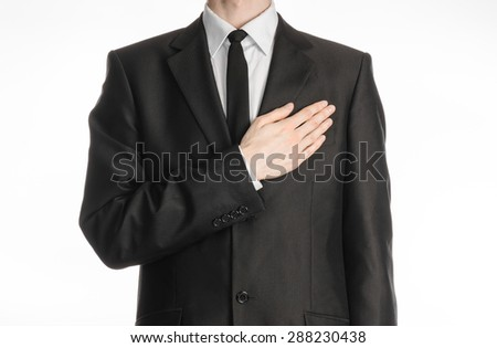 Businessman and gesture topic: a man in a black suit with a tie put his hand on his chest isolated on white background in studio