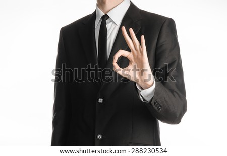 Businessman and gesture topic: a man in a black suit with a tie showing okay hand gesture on an isolated white background in studio - stock photo