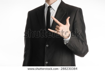 Businessman and gesture topic: a man in a black suit with a tie showing rock hand gesture on an isolated white background in studio - stock photo