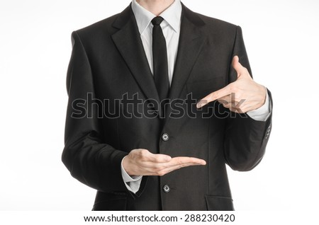 Businessman and gesture topic: a man in a black suit with a tie shows the left hand index finger on his right hand on a white isolated background in studio