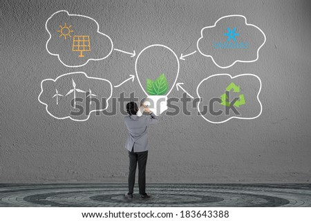 businessman and green energy concept on gray wall - stock photo