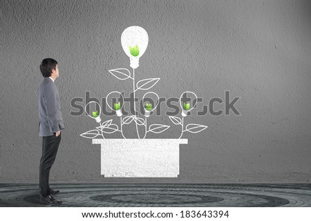 businessman and green energy concept on gray wall