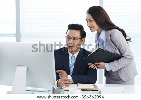 Businessman and his assistant looking at computer screen - stock photo