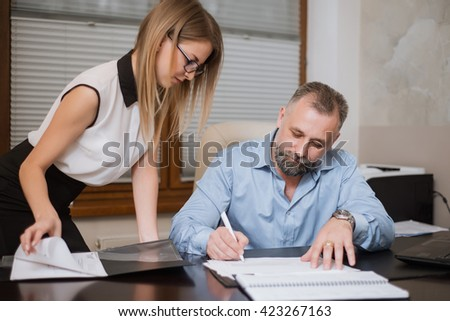 Businessman and his assistant Secretary in his office. The Secretary brought the boss documents to sign