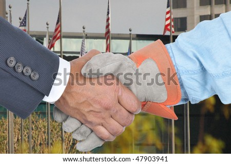 Businessman and laborer wearing a work glove handshake in front of a building with flags. Management and Labor negotiation concept. Hands and sleeves only in horizontal format. - stock photo