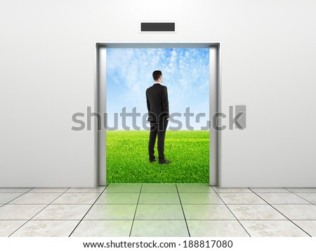 businessman and modern elevator with opened doors to field - stock photo