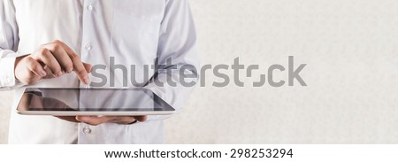 Businessman and searching information in a tablet Closeup image of male hand touching display of  computer against  texture wallpaper background Empty space for inscription or objects  - stock photo