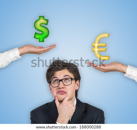 businessman and the choice between dollar or euro signs, blue background.