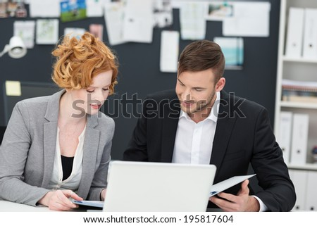 Businessman and woman at work sitting at a desk together discussing paperwork - stock photo