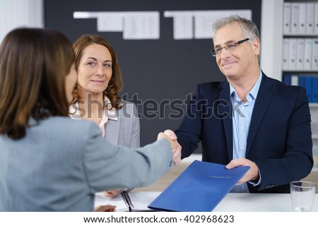Businessman and woman conducting an interview smiling as they congratulate and shake hands with the prospective applicant while holding her CV