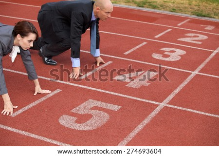 Businessman and woman on start line of running track - stock photo