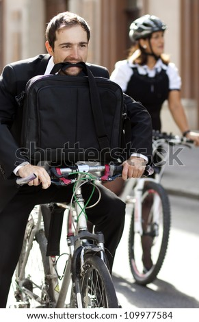 Businessman and woman racing on bikes - stock photo