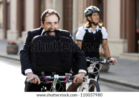 Businessman and woman racing on bikes - man holding suitcase in mouth - stock photo