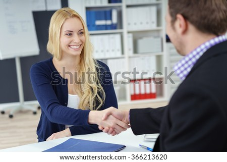 Businessman and woman shaking hands across an office desk as they seal a deal, in partnership, congratulations or in welcome, focus to attractive young woman - stock photo