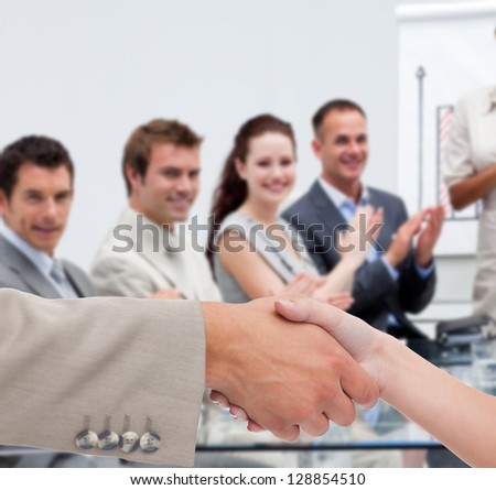 Businessman and woman shaking hands in presentation with business team clapping - stock photo