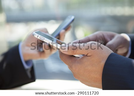 Businessman and woman sharing and exchanging data with smartphone.