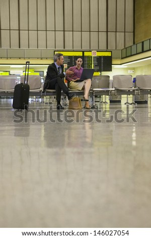 Businessman and woman using laptop in the airport lobby - stock photo