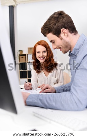 Businessman and woman working on a project sitting together at a desk analysing paperwork, focus to the attractive smiling young woman - stock photo