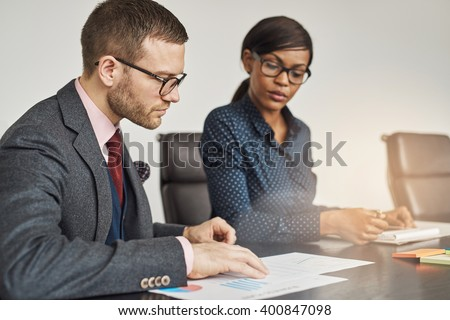 Businessman and women having a serious meeting sitting together reading a document or report with focus to a young man in glasses in the foreground - stock photo