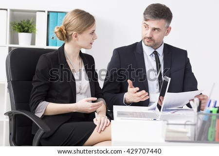 Businessman and young businesswoman sitting beside desk in light office
