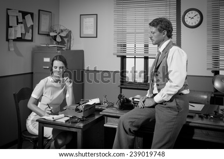 Businessman and young female secretary working in 1950s vintage office.