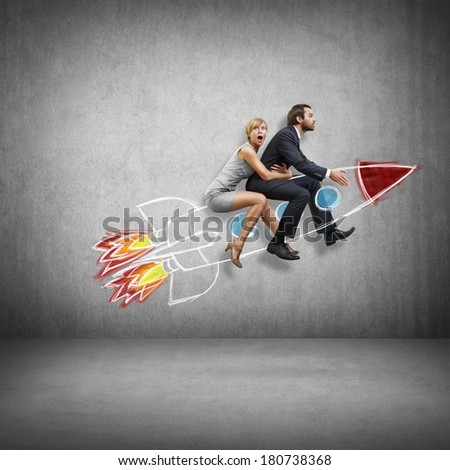 Businessman and young woman flying with rocket - stock photo
