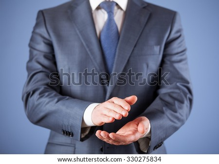 Businessman applauding - closeup shot on blue background - stock photo