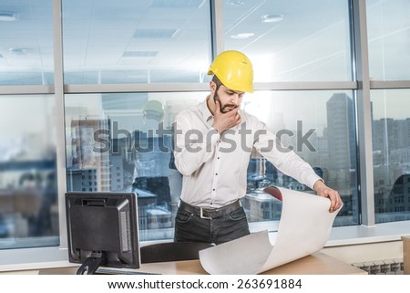 businessman architects look at paper plan business man architect near computer pc monitor in office to discuss business projects. Successful young engineer in construction yellow helmet are on table
