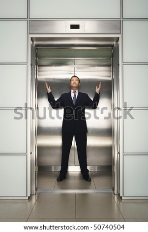 Businessman arms raised in Elevator, front view - stock photo