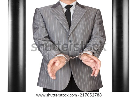 businessman arrested with handcuffs in jail isolated on white background with clipping path - stock photo