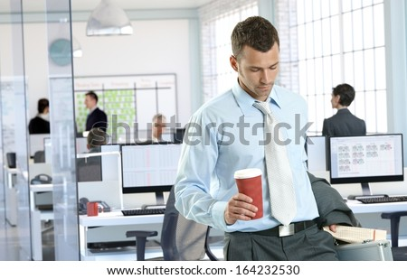 Businessman arriving to office holding coffee to go. - stock photo