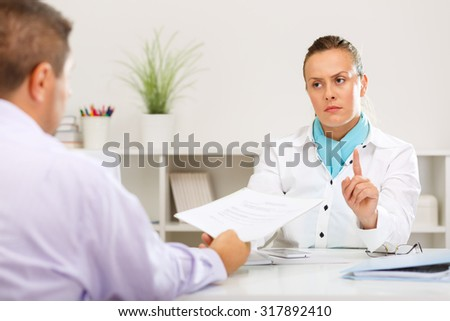 Businessman asking for a loan of a bank clerk, she denies the loan. - stock photo