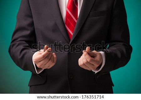 Businessman asking for money in black suit and red tie on green background. - stock photo