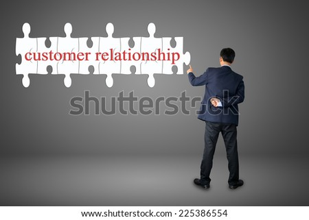 Businessman assembling complete a puzzle an insert word customer relationship  - stock photo