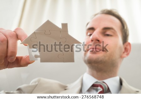 Businessman Assembling House Shape Puzzle On Glass - stock photo