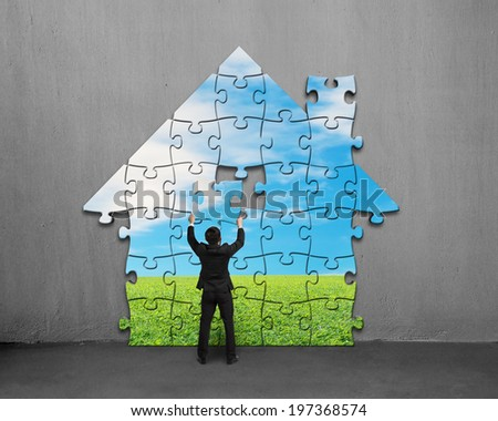 Businessman assembling house shape puzzles with beautiful landscape on concrete wall