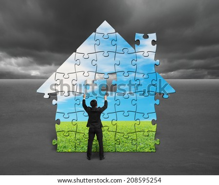 Businessman assembling house shape puzzles with nature image against cloudy sky