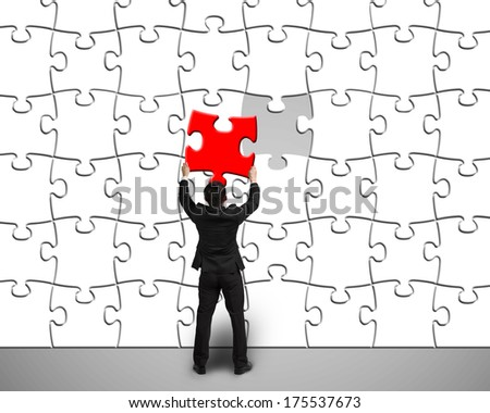 Businessman assembling unique red puzzle to white puzzles wall in gray background