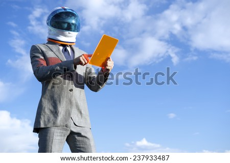 Businessman astronaut using futuristic tablet against bright blue sky