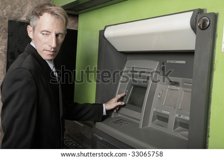 Businessman at an atm machine looking over his shoulder