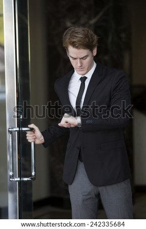 businessman at an entrance looking at his wristwatch - stock photo