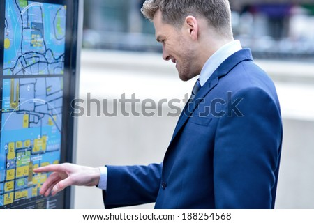 Businessman at bus stop reading a timetable - stock photo