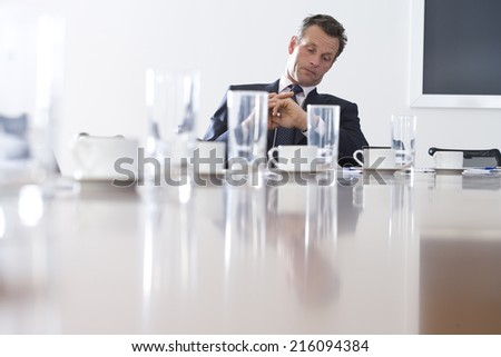 Businessman at conference table looking at watch, low angle view - stock photo