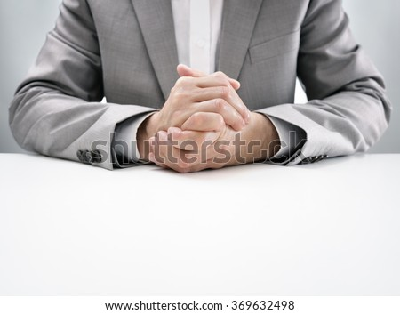 Businessman at desk in business job interview with hands clasped, attentive and listening in anticipation - stock photo