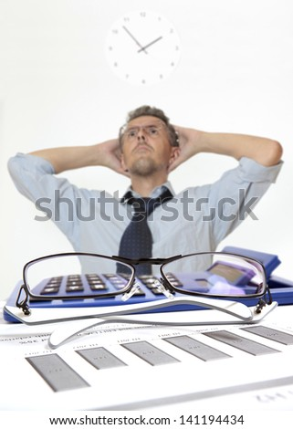 Businessman at desk in shirt and tie holding his head - stock photo