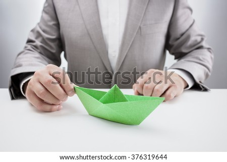 Businessman at desk with a green paper origami boat, concept for aspirations, leadership, strategy or just boredom in the office - stock photo