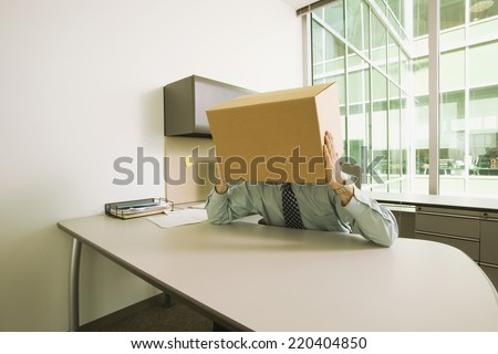 Businessman at desk with box on his head - stock photo