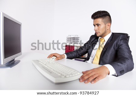 Businessman at his office using his desktop computer - stock photo