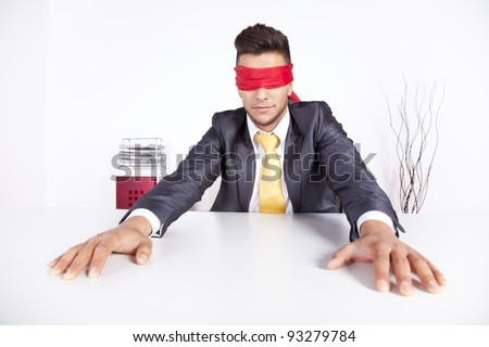 Businessman at his office with scarf covering his eyes - stock photo